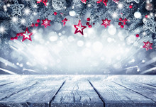 Festive Christmas Stage Scene  Background Framing. Fir Branches Decorated With Stars And Red Berries And Empty Wooden Flooring Platform. Beautiful Round Bokeh, Copy Space.