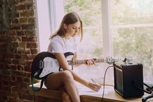 Woman In Headphones Recording Music Video Blog Home Lesson, Playing Guitar Or Making Broadcast Internet Tutorial While Sitting In Loft Workplace Or At Home. Concept Of Hobby, Music, Art And Creation.