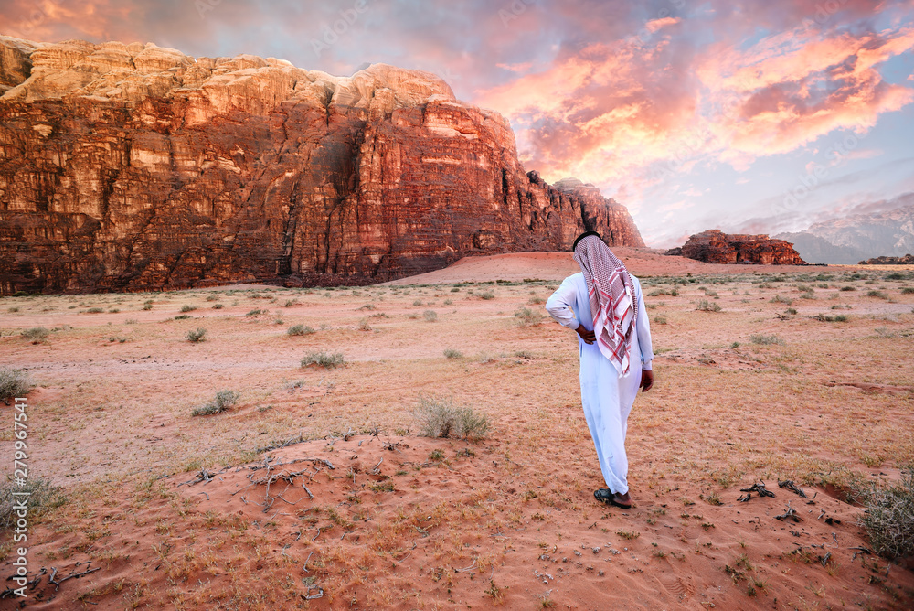 Fototapeta Arabian man in traditiona jordanian clothes (Keffiyeh - traditional Arabic headgear) walking in the wadi-rum desert at sunrise