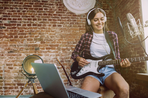 Woman in headphones recording music video blog home lesson, playing guitar or making broadcast internet tutorial while sitting in loft workplace or at home. Concept of hobby, music, art and creation. - 279967914