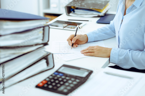 Unknown female bookkeeper or financial inspector calculating or checking balance, making report, close-up Canvas Print