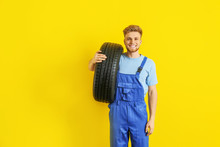 Young Male Mechanic With Car Tire On Color Background
