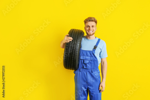 Fototapeta Young male mechanic with car tire on color background obraz