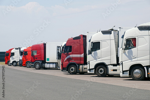 Various types of trucks in the parking lot next to the motorway. Fotobehang