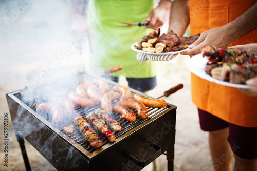 Friends having a barbecue party in nature while having fun - 279973106