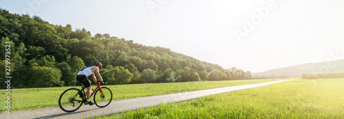 Cuadros en Lienzo  Panorama shot of cyclist on racing cycle in a rural landscape in summer with sce