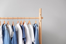 Rack With Hanging Clothes On Light Background