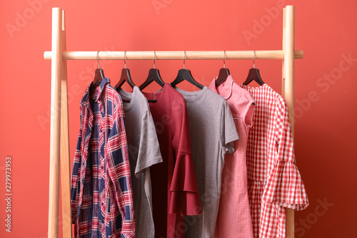 Fényképezés  Rack with hanging clothes on color background