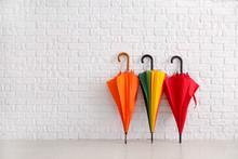 Stylish Umbrellas Near White Brick Wall