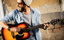 Handsome Man Playing Guitar On The Street On Summer Day