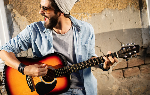 Fototapeta Handsome man playing guitar on the street on summer day
