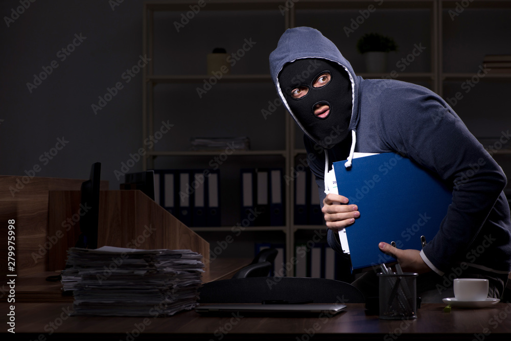 Fototapeta Male thief in balaclava in the office night time