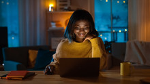 Portrait Of Beautiful Black Girl Uses Computer While Sitting At Her Desk At Home, She's Wearing Warm Sweater. In The Evening Creative Woman Works On A Computer In Her Cozy Living Room.