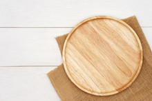 Empty Round Wooden Plate With Rustic Brown Burlap Cloth On White Wooden Table. Top View Image.
