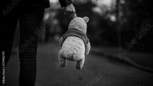 Fotografie, Obraz Woman holding in her hand a Winnie the pooh plush, France.
