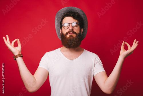 Recess Fitting Zen Portrait of handsome man doing zen gesture, calming, over red background