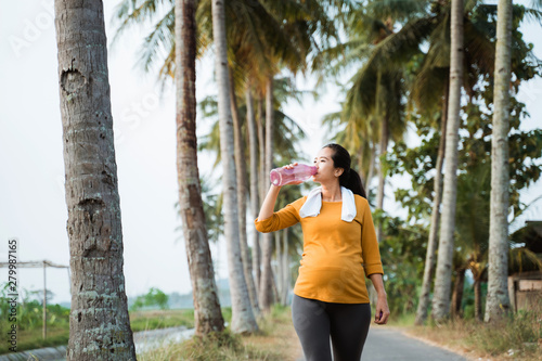 Cuadros en Lienzo thirsty pregnant woman after workout drinking a bottle of water