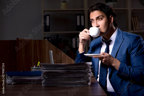 Young male employee working night in the office