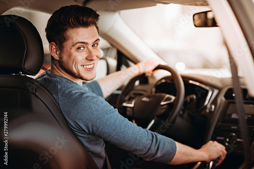 Happy young driver behind the wheel of a car. Buying a car and driving concept.