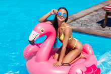Young And Sexy Girl Having Fun And Laughing And Having Fun In The Pool On An Inflatable Pink Flamingo In A Bathing Suit And Sunglasses In Summer.