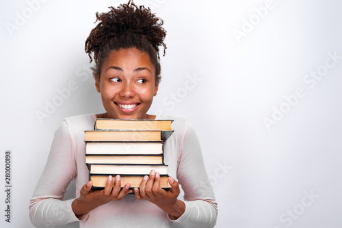 Fotografia Portrait of happy nerd young girl holding books over white background