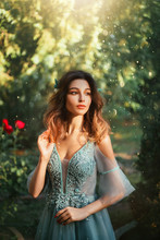 Tender Girl With Cute Doll Fair Face And Short Dark Hair, Princess In Light Blue Dress With Open Shoulders, Elegant Lady In Garden With Green Trees And Red Roses On Background, Art Portrait.
