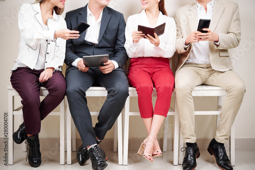 Aluminium Prints Akt Close-up of young businessmen and businesswomen sitting on chairs and using their gadgets tablet pc and mobile phone
