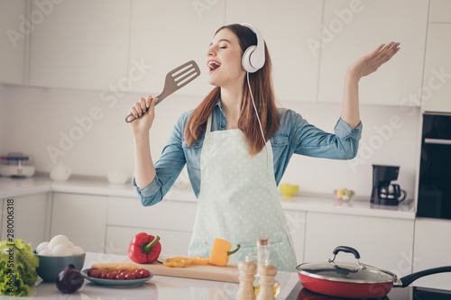 Photo of wife begin prepare family dinner singing like rock star with kitchenware utensil overjoyed earflaps playlist - 280006318