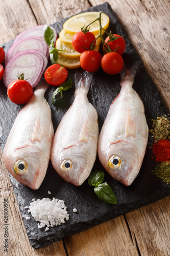 gilt-head sea bram fish with ingredients close-up on a slate board Canvas Print