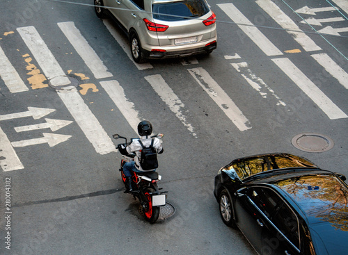 Fototapeta  Motorcyclist and black and gray cars are at a pedestrian crossing at a traffic l
