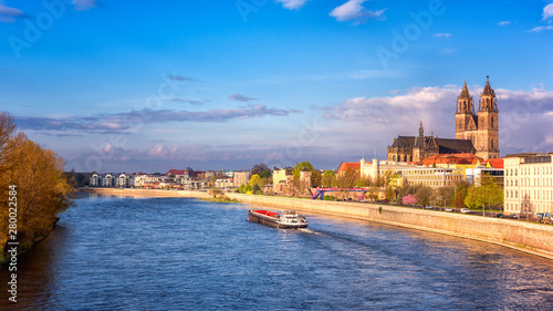 Foto auf AluDibond Schiff View of Magdeburg with cathedral, river Elbe and cargo boat, beautiful bright morning cityscape with blue sky and clouds, Saxony, Germany. Outdoor travel background