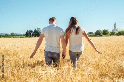 Photo couple qui se tiens par la main de dos dans un champs de blé - au loin on voit l