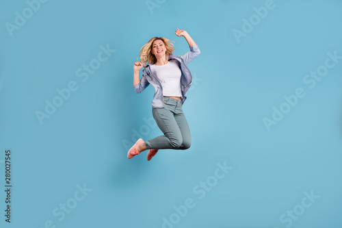 Obraz Full body photo of pretty lady raising arms wearing pants trousers isolated over blue background - fototapety do salonu