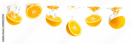 Bunch of organic orange halves sinking into crystal clear water with air bubbles. Panoramic view