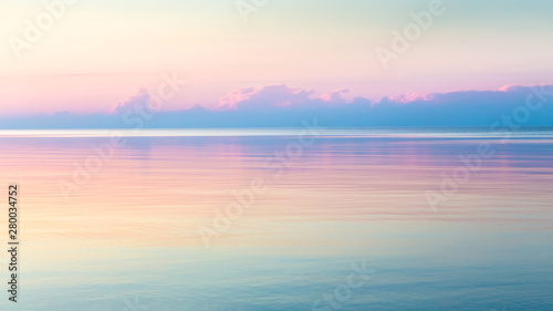 Tuinposter Zonsondergang Morning clear seascape with colorful sky. Natural soft background. Beautiful magical pink and gold reflected in the water.