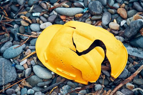 Fotografia  Cracked work helmet on the floor covered with pebble stones