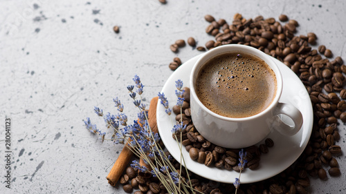 Close-up of white espresso coffee Cup , scattered roasted coffee beans and cinnamon, copy space