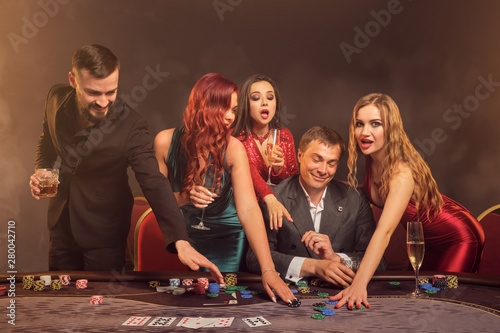 Fototapeta Group of a young wealthy friends are playing poker at a casino. obraz na płótnie