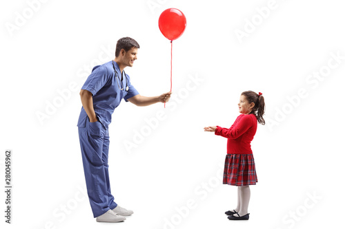 Photo  Male doctor giving a red balloon to a little girl