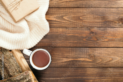 Poster de jardin The Autumn composition. Frame made of white knitted sweater, cup of tea, firewood on wooden background. Cozy autumn or winter holiday concept. Flat lay, top view, copy space