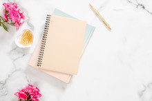 Blank Paper Notebook, Pink Flowers, Golden Stationery On Marble Background. Flat Lay, Top View Feminine Home Office Desk.