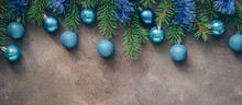 Christmas Border, Fir Branches Decorated Blue Balls And Tinsel On A Dark Textured Rustic Background. Top View, Flat Lay, Copy Space.