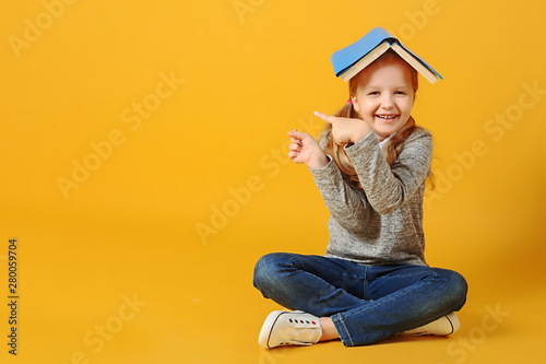 Fotografía Cheerful attractive little student girl is sitting on the floor with a book on her head and pointing to the side
