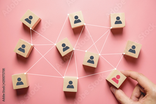 Obraz na plátně Building a strong team, Wooden blocks with people icon on pink background, Human resources and management concept