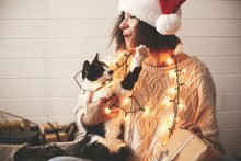 Cute Cat Playing With Santa Hat On Stylish Happy Girl In Festive Christmas Lights On Background Of Modern Presents. Young Funny Woman In Cozy Sweater Playing With Kitty. Happy Holidays