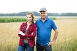 Two farmers standing against wheat field