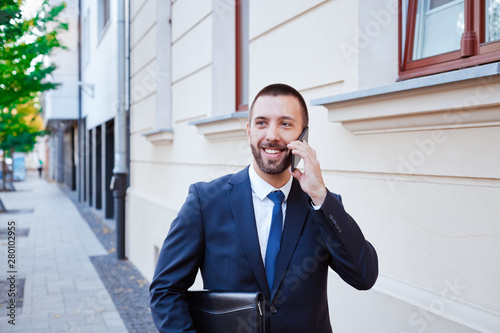 Fototapety, obrazy: Smiling young businessman talking on phone in the city