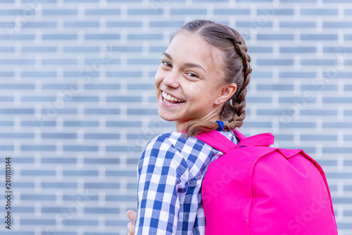 Obraz Beautiful student teenager schoolchild with backpack looking at camera. Smiling cute child with bag. Teen girl with braided hair against a brick wall outdoors. Childhood and Back to school concept. - fototapety do salonu