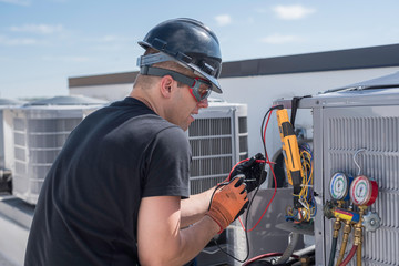Hvac repair man working with tools on condenser