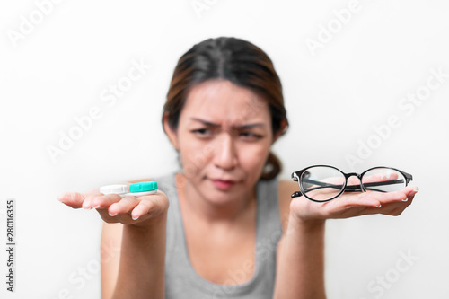 Fotomural Asian woman holding glasses and contact lens on white background, Selective focus on glasses , myopia and eyesight problem concept